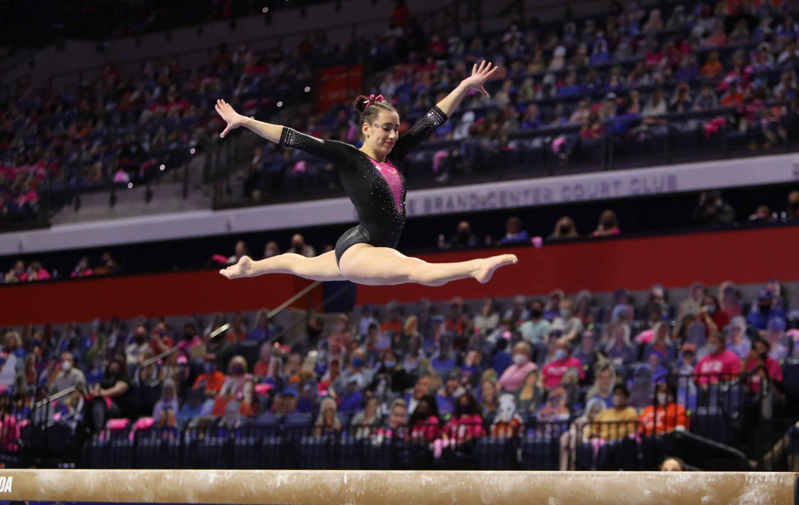 Leah Clapper leaping on beam during the 2021 link to pink meet